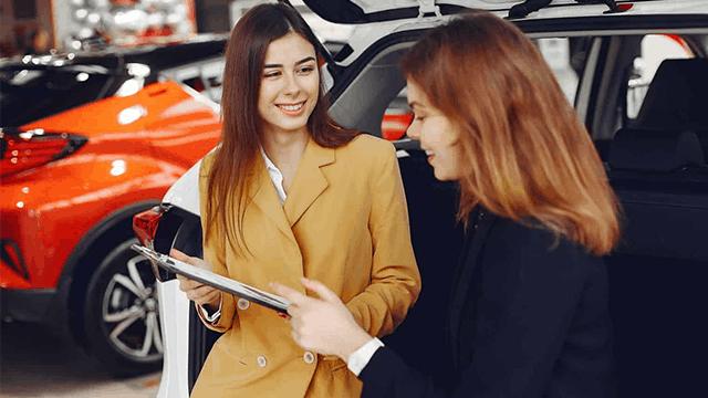 Women meeting at car dealership