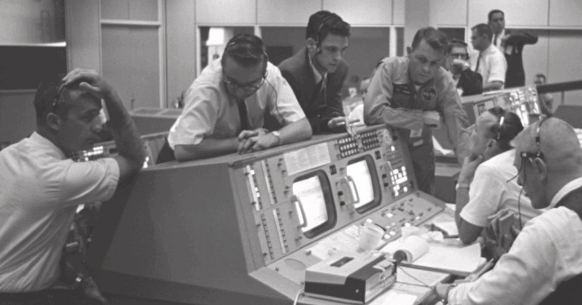 Men working around old computer